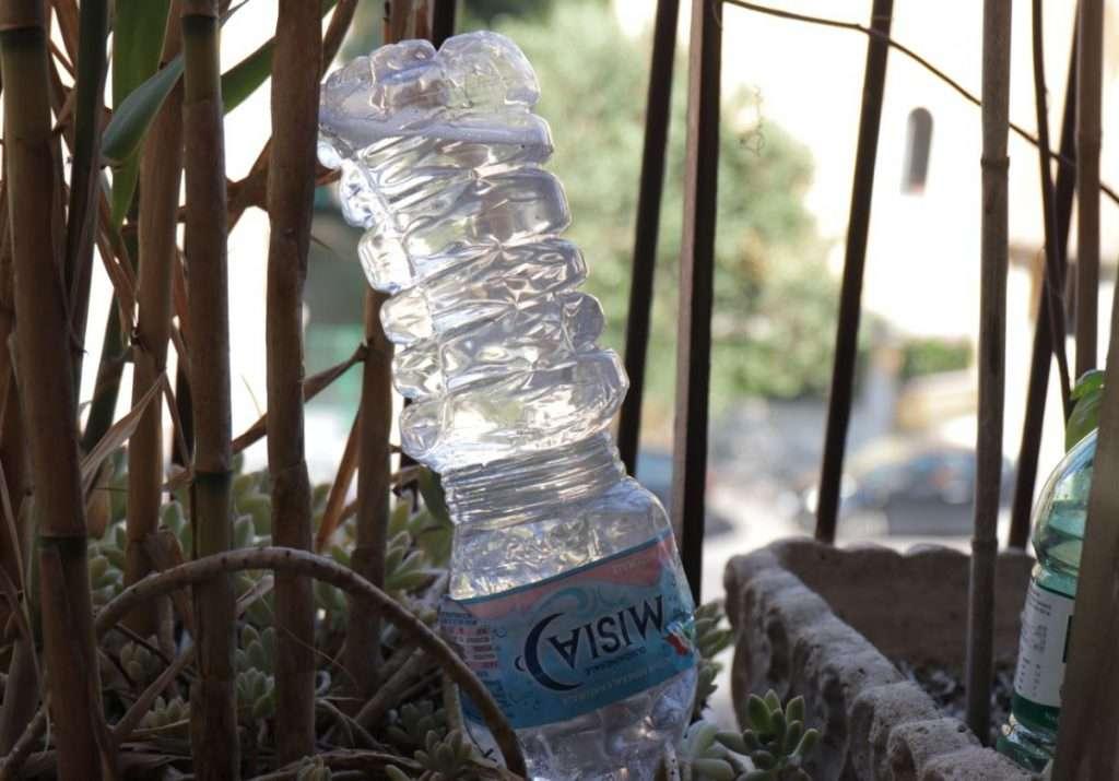 Bottiglia a testa in giù con foro sul tappo