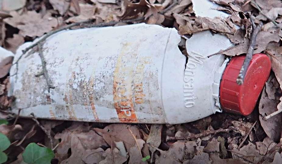 Una bottiglia di erbicida abbandonata in un bosco